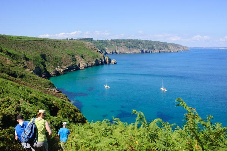 Des touristes randonnant sur les collines près du Cap de la Chevre avec une belle vue sur une baie avec voiliers blancs. Bretagne, France. Arrière-plan vacances en famille actif.