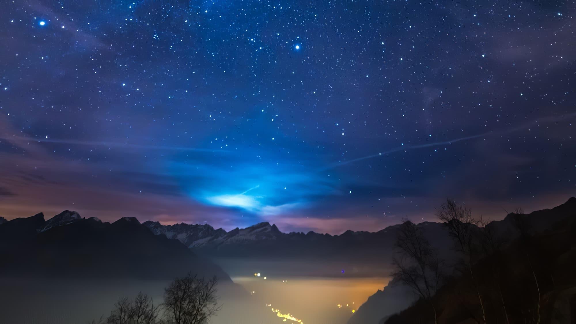 Le magnifique ciel étoilé de Noël et le majestueux massif des Alpes françaises italiennes, avec des villages scintillants en contrebas et des lumières lunes derrière les nuages.
