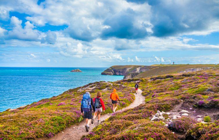 Touristes randonnant le long des belles côtes de Bretagne au célèbre point de vue de la péninsule du Cap Frehel avec phare traditionnel en arrière-plan par jour ensoleillé avec ciel bleu et nuages en été, France