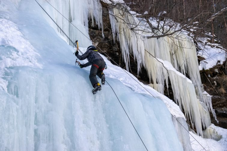 Homme escaladant une cascade de glace