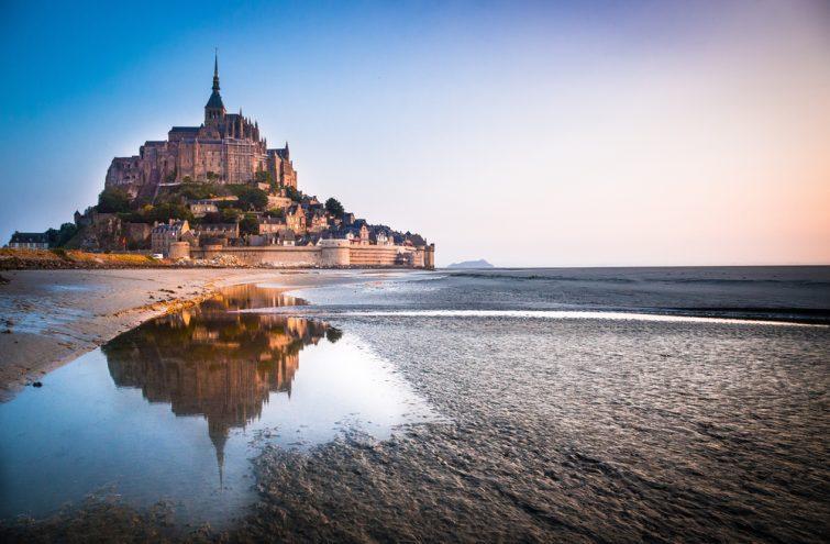 Normandie, France. Le Mont Saint Michel se reflétant dans la mer au lever du soleil.